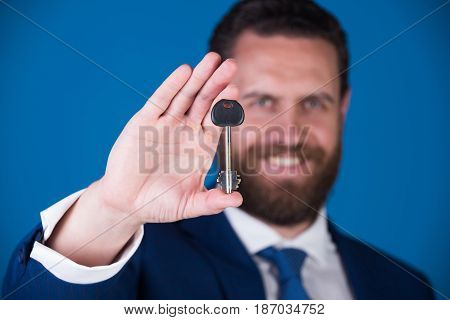 key in hand. businessman or man with key in suit on blue background deposit and credit reward and promotion stock photo