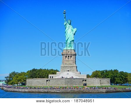 NYC New York city Statue of Liberty on Liberty island. Statue of Liberty National Monument and museum. Statue of Liberty island green garden. Famous sightseeing NYC places for tourists. NYC boat trips