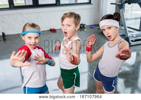Group of little kids in sportswear exercising and posing at camera in gym children sport school concept stock photo