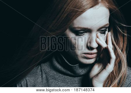 Beautiful young woman covering her tears black background stock photo