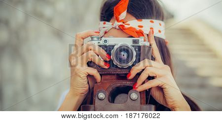 Beautiful woman taking photo with old fashioned film camera. Close up stock photo