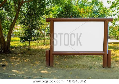 Blank wood board in the public park with green trees background.