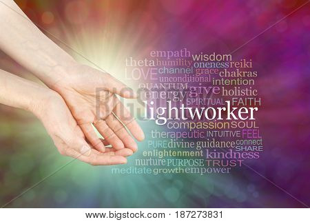 The healing hands of a Lightworker  - Female hands in open gesture beside the word LIGHTWORKER and a relevant word cloud  on a radiating multi-coloured bokeh background stock photo