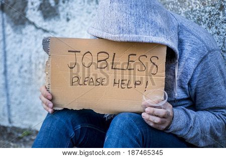 Jobless man begging on a street holding a handwritten sign for help covering his face as he sits on the sidewalk in jeans and a hoodie holding a cup for coins stock photo