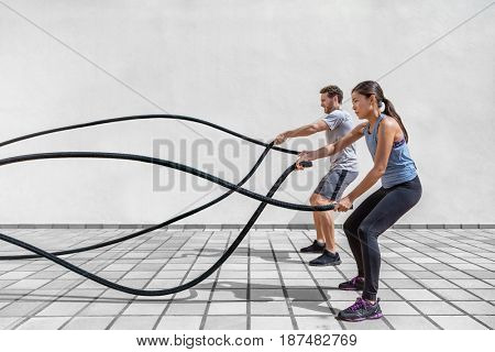 Fitness people exercising with battle ropes at gym. Woman and man couple training together doing bat