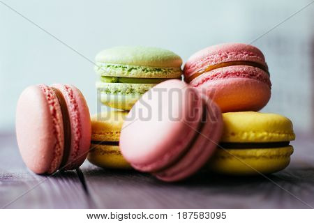 Fresh baked colored macaroon pastry cookies macarons, macaroni on a white plate close up, low angle view. stock photo