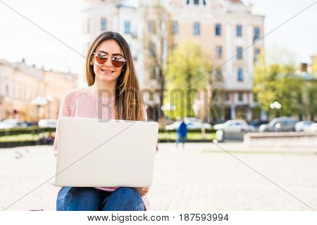 Attractive girl is doing university project on a laptop outside on a sunny day. She is wearing casual clothes and sunglasses . stock photo