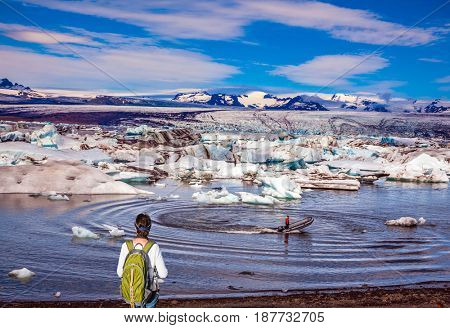 The woman - tourist with green backpack watching the sunrise in Ice Lagoon. The concept of extreme northern tourism. Ice floes are reflected in the water  stock photo