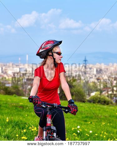 Escape urban . Bicycle girl has rest from city bustle. Woman wearing sport helmet rides returns into urbanization . Factory pipes in background. stock photo