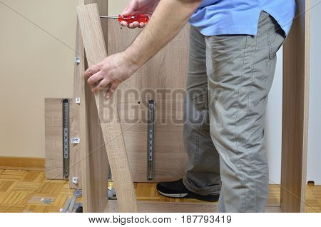 Man standing by elements of furniture ready to be assembled stock photo