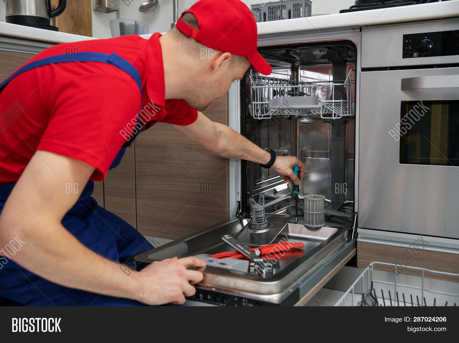 adult,appliance,caucasian,dishwasher,domestic,fix,fixing,handyman,holding,home,house,kitchen,maintenance,male,man,open,overall,people,person,profession,red,repair,repairing,repairman,screwdriver,service,serviceman,technician,uniform,work,worker