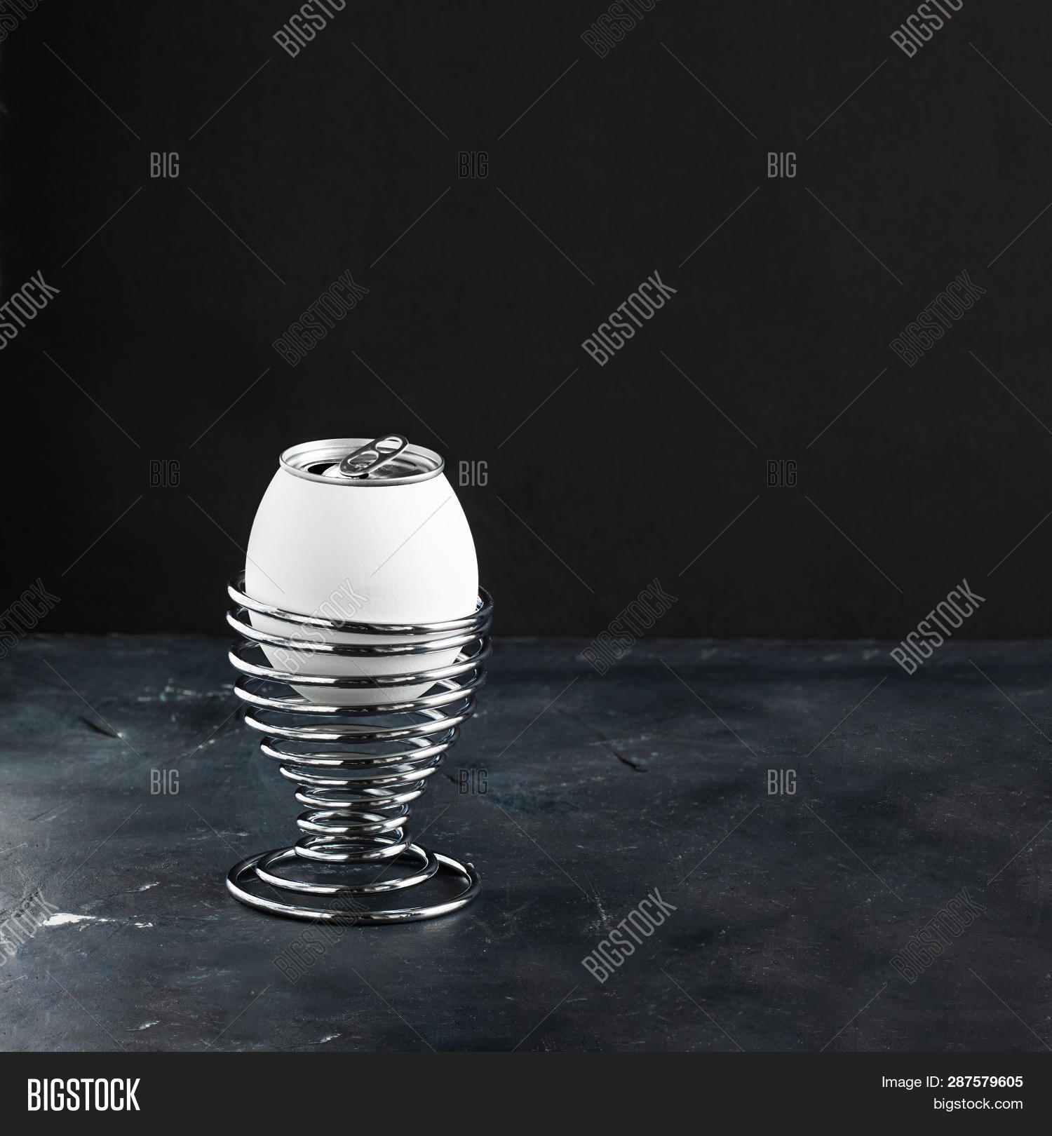 White Egg In Metal Helix Egg Cup, Opened Lemonade Alluminium Can As Top Of Egg On Black Chalkboard B