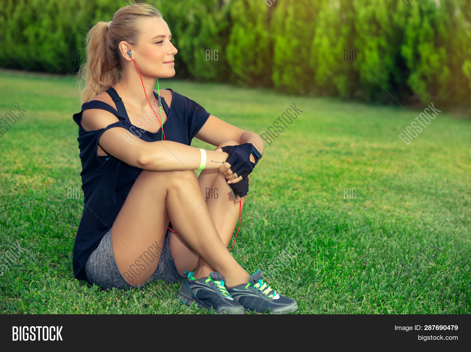 Female exercising outdoors, pretty blond woman relaxing after a good workout, listening music and me