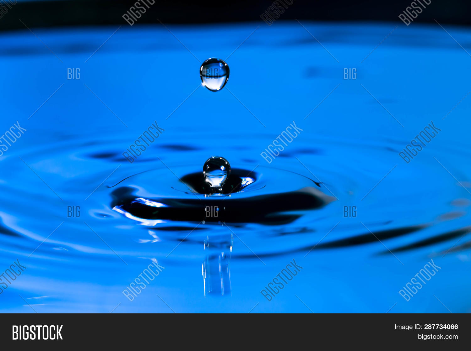 Closeup Water Drop Falling And Dripping From The Top To The Surface Of Water That Makes Two Water Dr