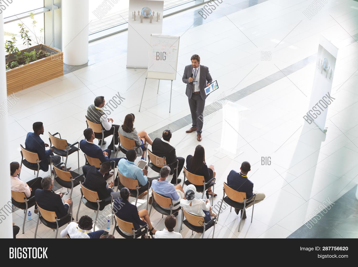 High angle view of male caucasian speaker with digital tablet speaks with microphone in a business s