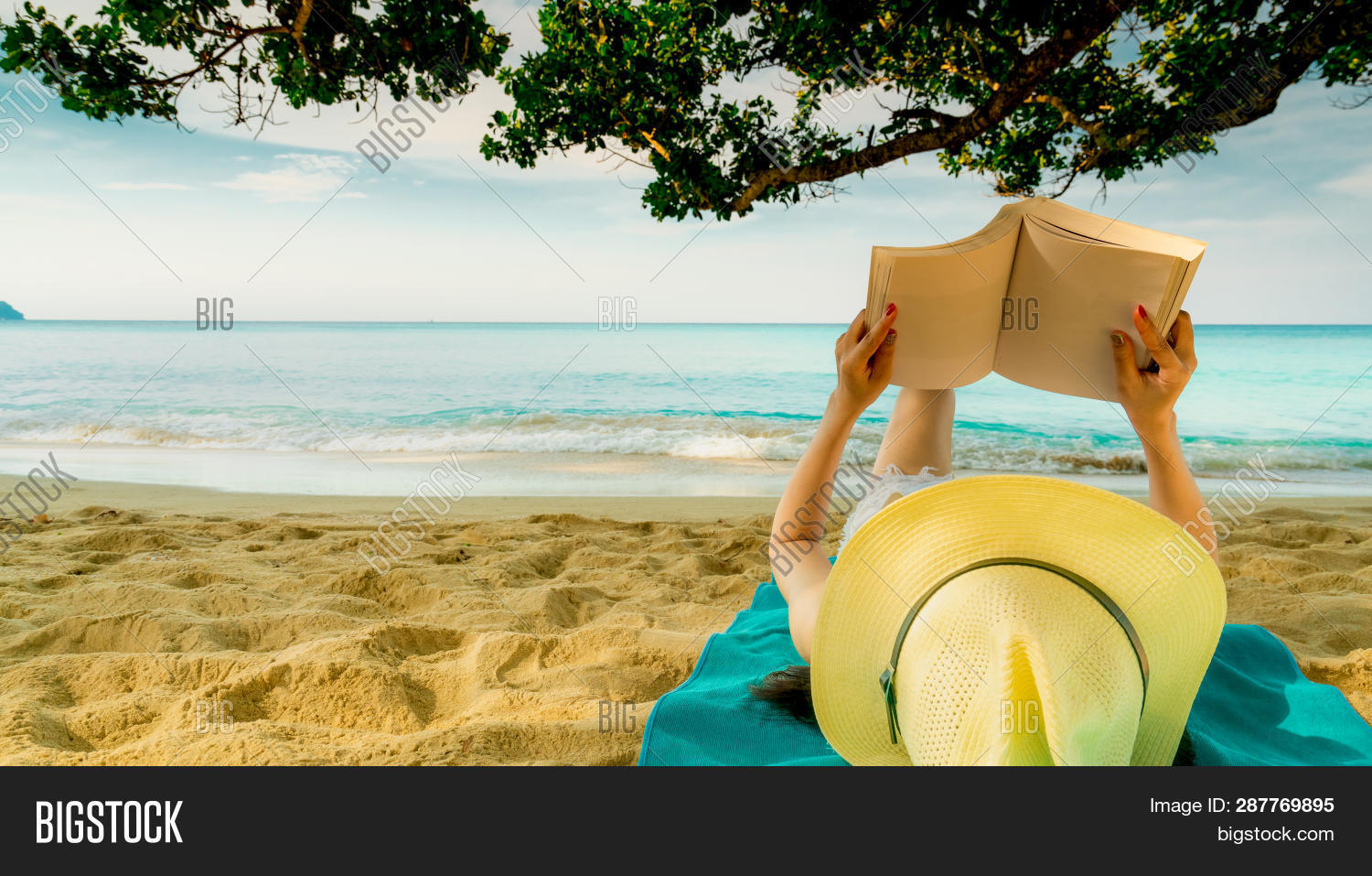 Woman Lie Down On Green Towel That Put On Sand Beach Under The Tree And Reading A Book. Slow Life On