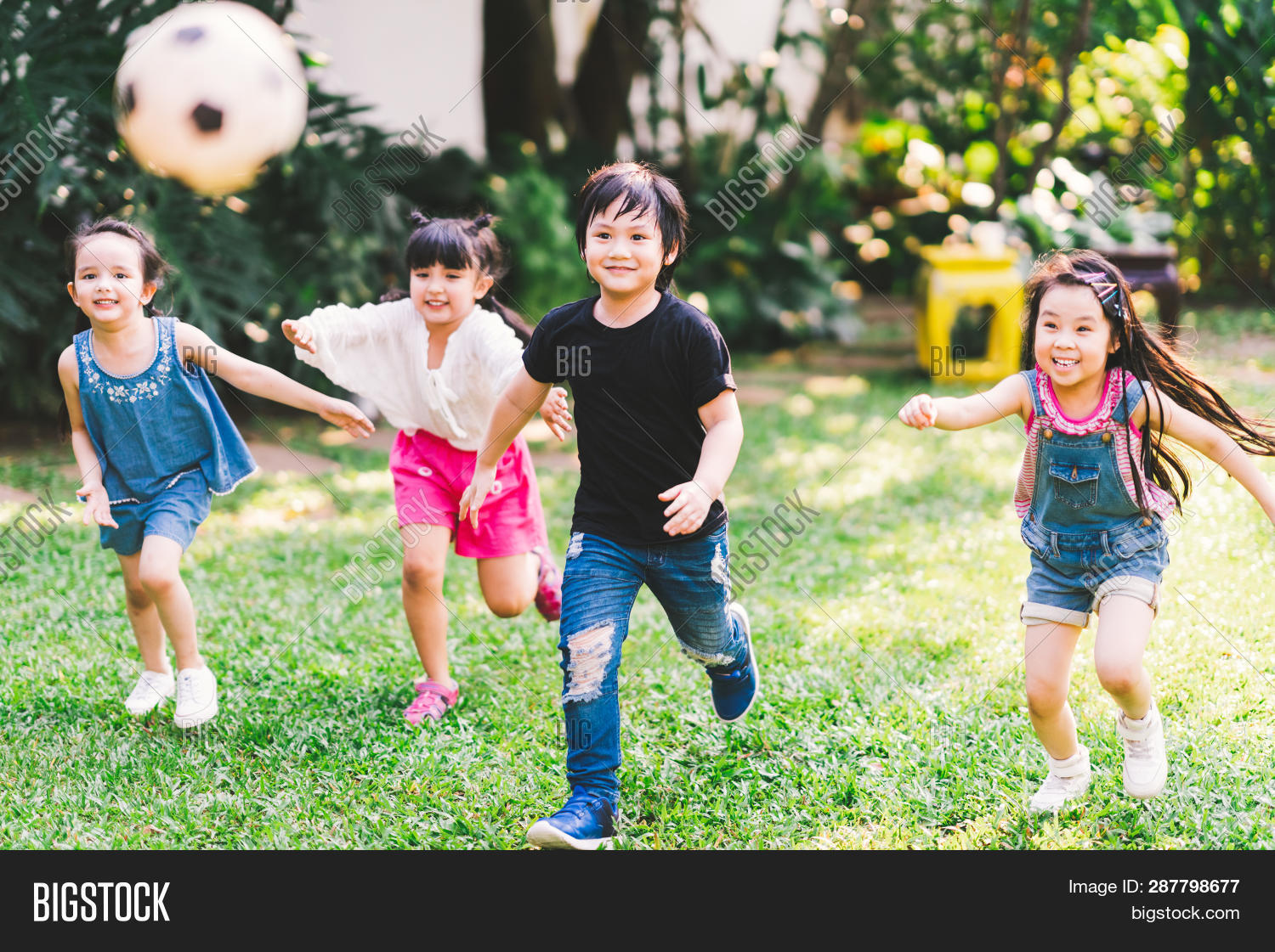 Asian And Mixed Race Happy Young Kids Running Playing Football Together In Garden. Multi-ethnic Chil