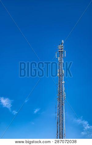Communications mast set against a blue summer sky stock photo