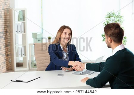 Human resources manager shaking hands with applicant before job interview in office stock photo