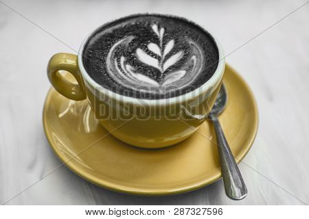 Charcoal latte coffee cup latest food trend. Activated charcoal powder mixed in cappuccino steamed milk froth for healthy detox hangover cure. stock photo