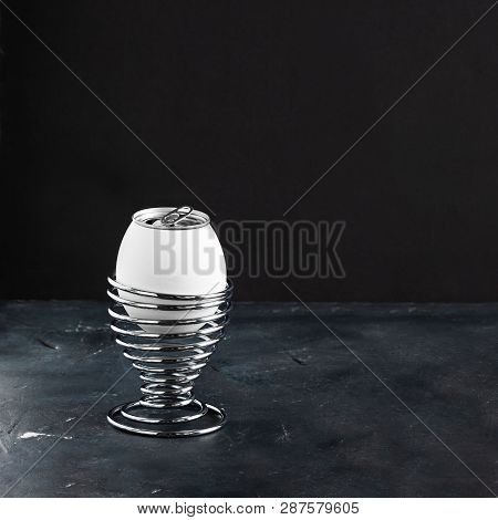 White egg in metal helix egg cup, opened lemonade alluminium can as top of egg on black chalkboard background with copy space, Creative concept for breakfast and Easter, Square stock photo
