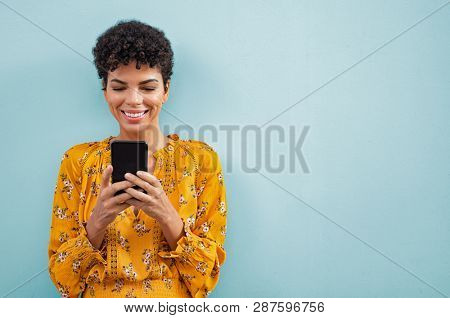 Happy smiling black woman using smart phone. Young brazilian woman writing a message with mobile iso