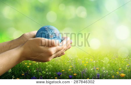 Earth day holiday concept.Close up image of human hands holding  planet earth against green nature