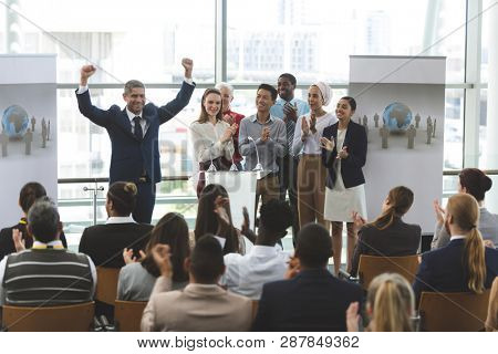 Front view of mixed race businessman standing at podium with diverse colleagues holding his arms up in victory while he speaks at business seminar in office building stock photo