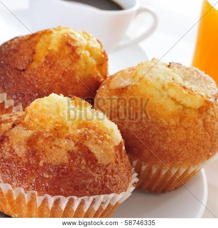 a plate with some magdalenas, typical spanish plain muffins, and a cup of coffee and a glass of orange juice stock photo