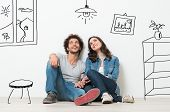 Portrait Of Happy Young Couple Sitting On Floor Looking Up While Dreaming Their New Home And Furnish