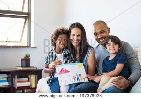 Proud parents showing family painting of son sitting on sofa at home. Smiling mother and father with