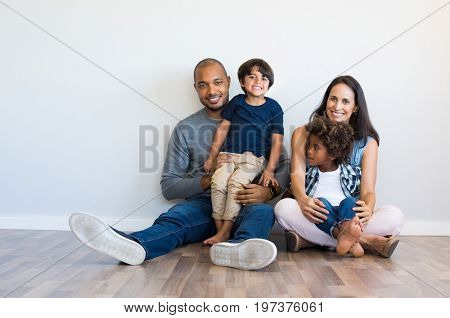 Happy multiethnic family sitting on floor with children. Smiling couple sitting with two sons and lo