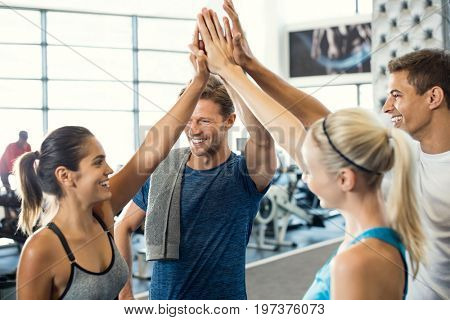 Smiling men and women doing high five in gym. Group of young people making high five gesture in gym