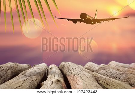 Airplane flying over tropical beach smooth wave and sunset sky abstract background. Copy space of empty old wood table business summer vacation and travel adventure concept.Vintage tone filter color. stock photo