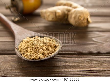 Spice ginger powder in a wooden spoon on dark wooden background vintage hand mill and ginger root. Close-up. stock photo