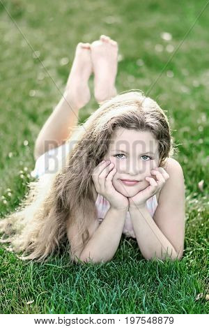 little beautiful girl with long hair on green grass at summer day stock photo