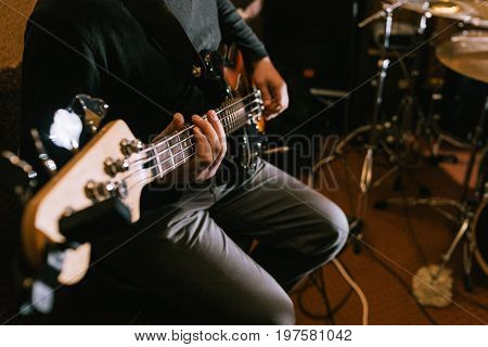 Guitarist playing bass guitar in studio closeup. Music band recording process, live rock concert stock photo
