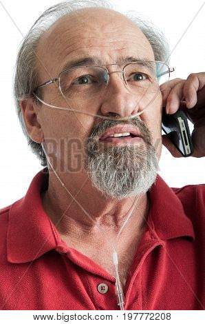 Elder man with COPD talking on the phone while wearing an oxygen cannula for supplemental air. stock photo
