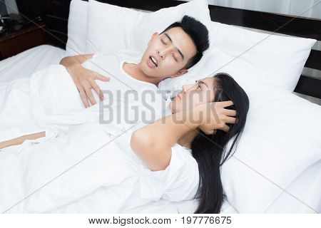 Couple in bed man snoring on the bed in the bedroom and woman can not sleep stock photo