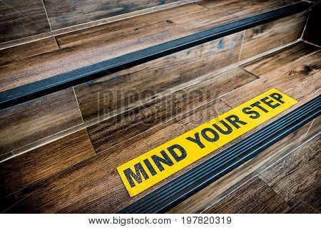 Mind your step sticker sign pasted on wooden stair. Warnings abstract or indoor architecture concept stock photo