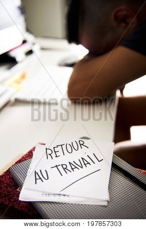 closeup of a concerned man sitting at his office desk and a note in the foreground with the text retour au travail, back to work written in french stock photo