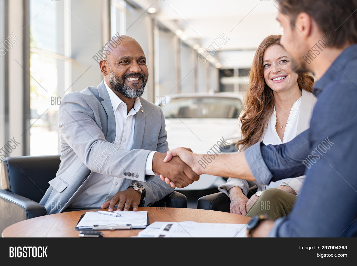 Smiling couple buying a new auto at car showroom. African salesman making handshake with young man p