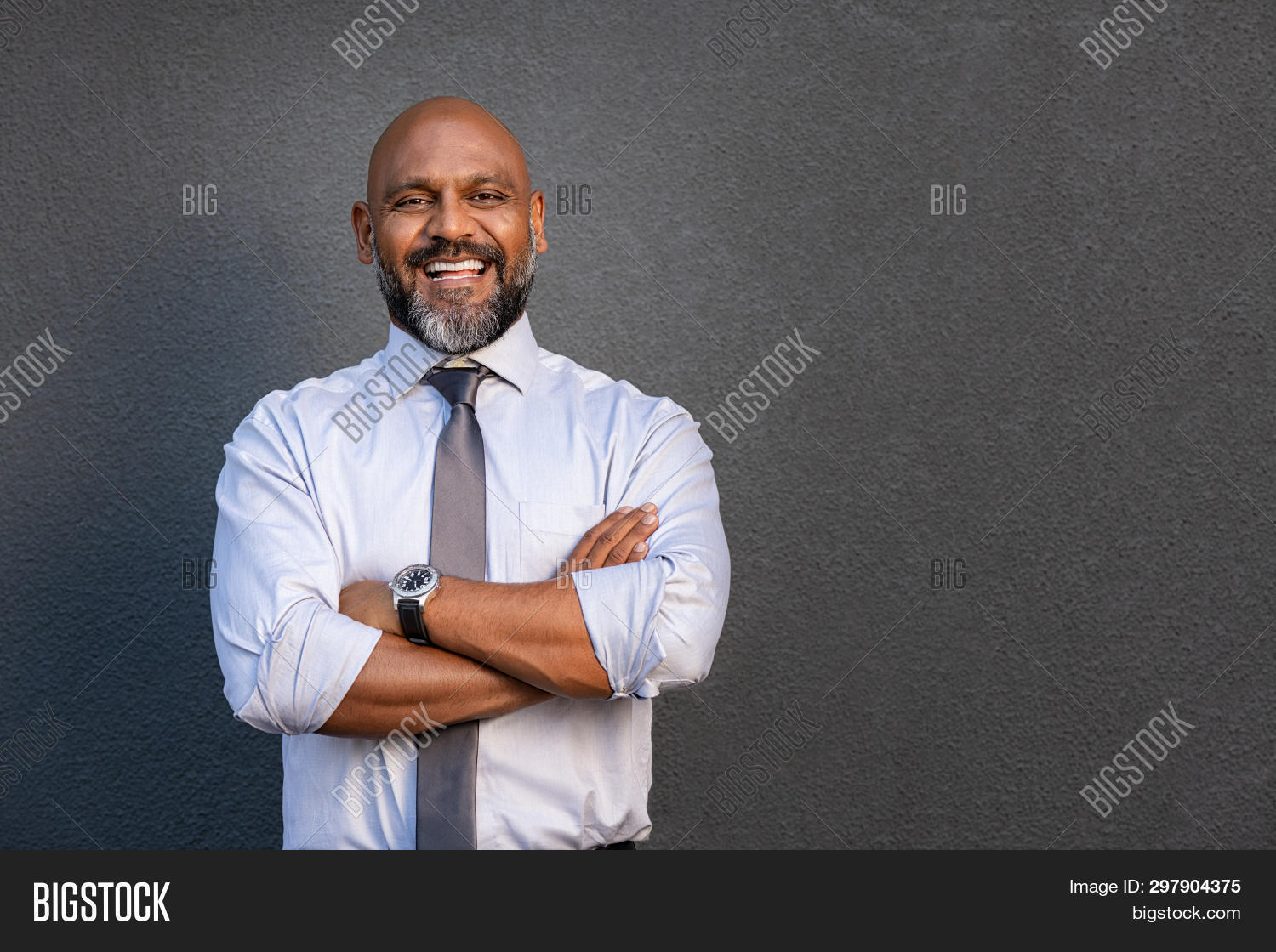 Successful senior man with folded arms standing over grey background. Mature black businessman in sh
