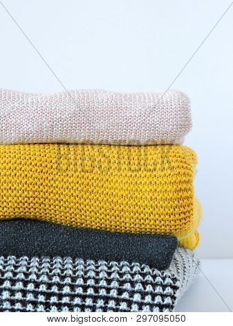 Stack of various sweaters isolated on white background. Knitted wool sweaters. A stack of knitted sweaters. The concept of warmth and comfort, closeup. Cloth knitted background. Space for text. stock photo