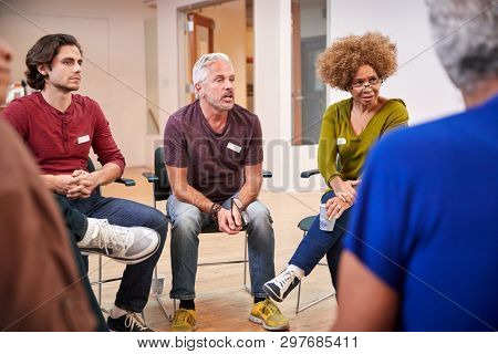 People Attending Self Help Therapy Group Meeting In Community Center stock photo