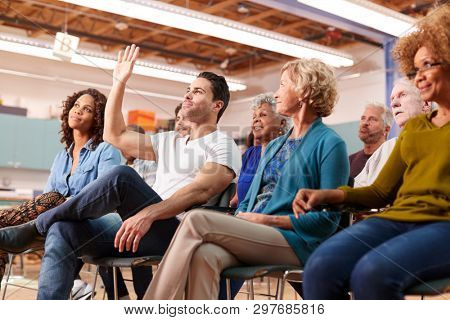 Man Asking Question At Neighborhood Meeting In Community Center stock photo