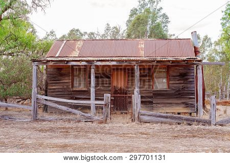 An old abandoned falling down timber slab hut with iron roof disused in the Australian countryside stock photo