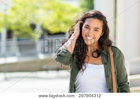 Happy young beautiful woman walking on the street. Portrait of cheerful university student looking a