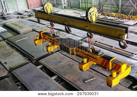 Overhead traveling crane with magnetic grippers traverse for lifting steel sheets. Industrial indoors area. stock photo
