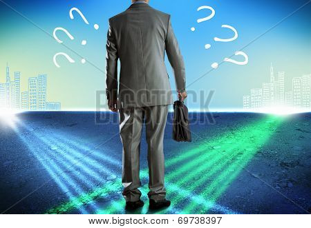 Rear view of uncertain businessman with briefcase stock photo